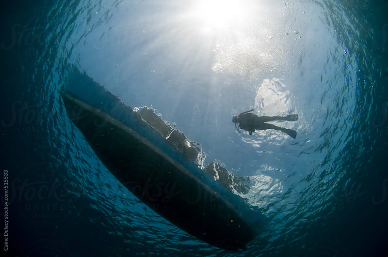 Scuba Divers and boat from below looking up by Caine Delacy for Stocksy United