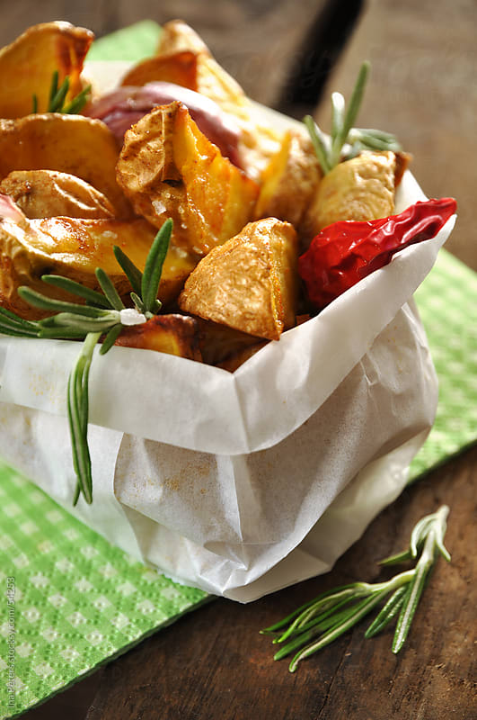 Food: Homemade potatoe wedges in a paper bag with rosemary garli by Ina Peters for Stocksy United