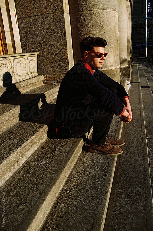 Young hipster man sitting on the stairs  by Painted Wood for Stocksy United