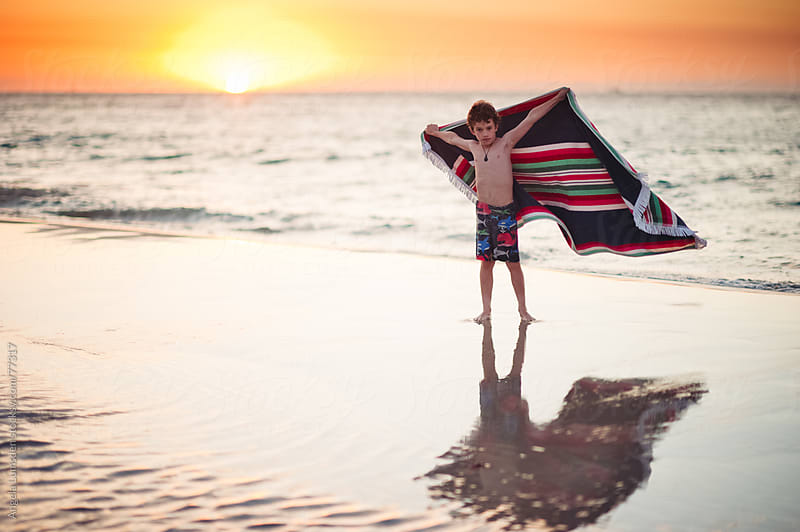 Boy standing with an outstretched towel at the beach at sunset by Angela Lumsden for Stocksy United
