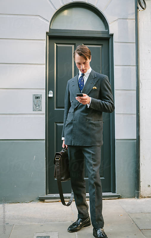 Elegantly dressed businessman checking his mobile phone. by kkgas for Stocksy United