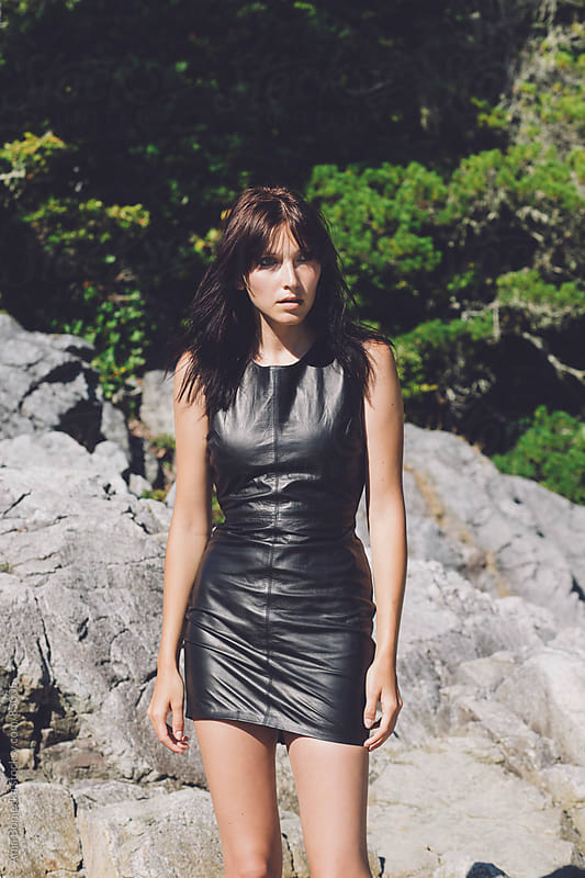 A beautiful girl in a leather dress by large rocks outside  by Ania Boniecka for Stocksy United
