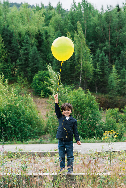 young boy smiling and holding a yellow balloon by Tara Romasanta for Stocksy United