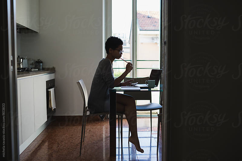Silhouette of woman working on laptop by michela ravasio for Stocksy United