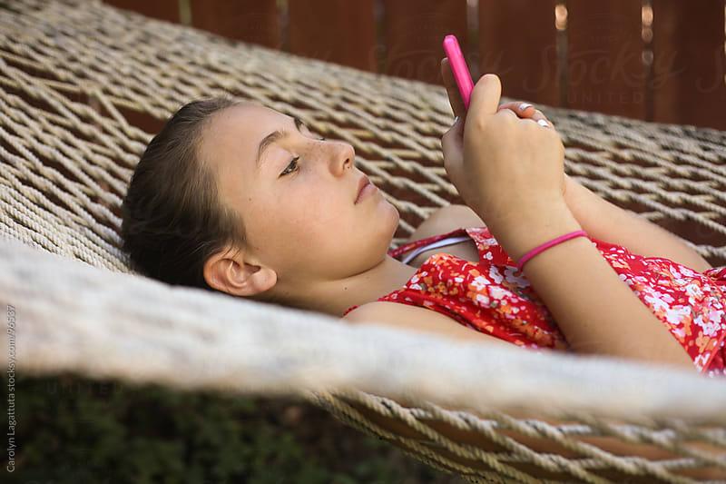 Young girl laying on a hammock texting by Carolyn Lagattuta for Stocksy United