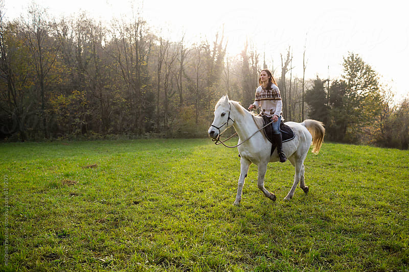 Young woman riding a horse in a meadow by michela ravasio for Stocksy United