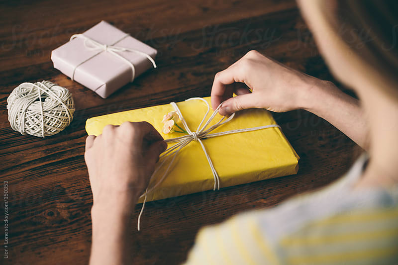 Over the shoulder of woman wrapping gifts by Lior + Lone for Stocksy United