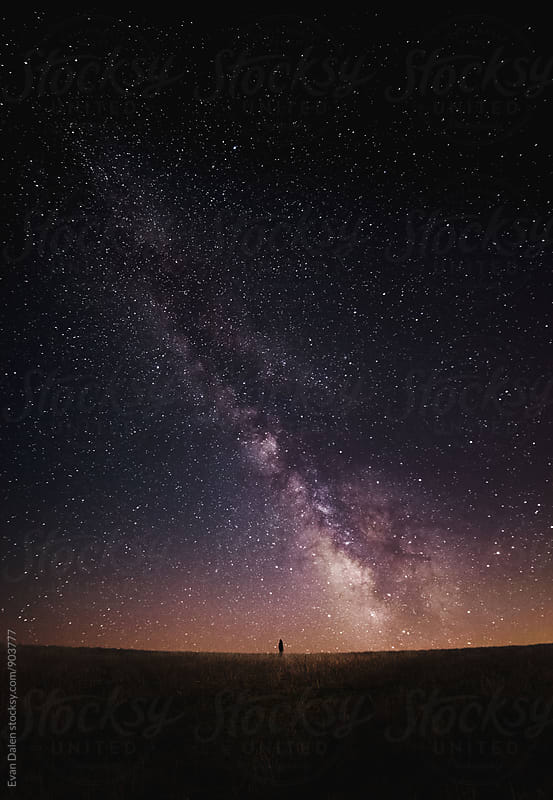 Milky Way Galaxy Over Field with Small Person by Evan Dalen for Stocksy United