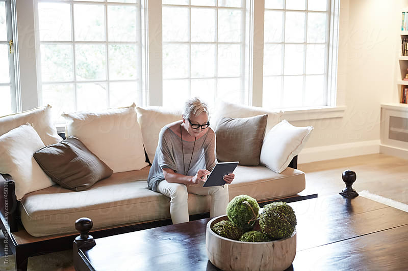Mature woman with grey hair using digital tablet in luxury living room by Trinette Reed for Stocksy United