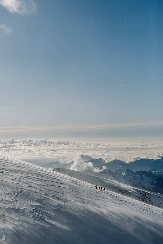 Group of skiers walking up the glacier in windy day by Blue Collectors for Stocksy United