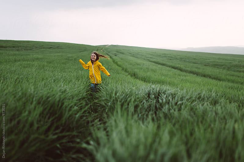 Girl with raincoat playing on the field. by Dejan Ristovski for Stocksy United