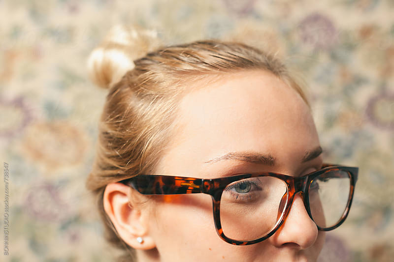 Closeup of a woman wearing glasses in front of a vintage wall. by BONNINSTUDIO for Stocksy United
