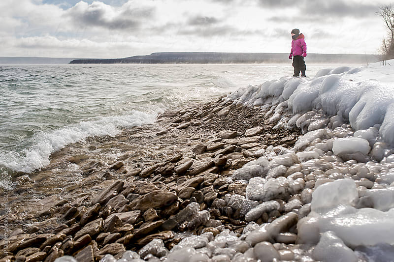 Young Child Looking Out Over Lake From Freezing Cold Lakeshore in Winter by JP Danko for Stocksy United