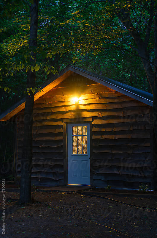 exterior of a cabin in the woods at night by Deirdre Malfatto for Stocksy United
