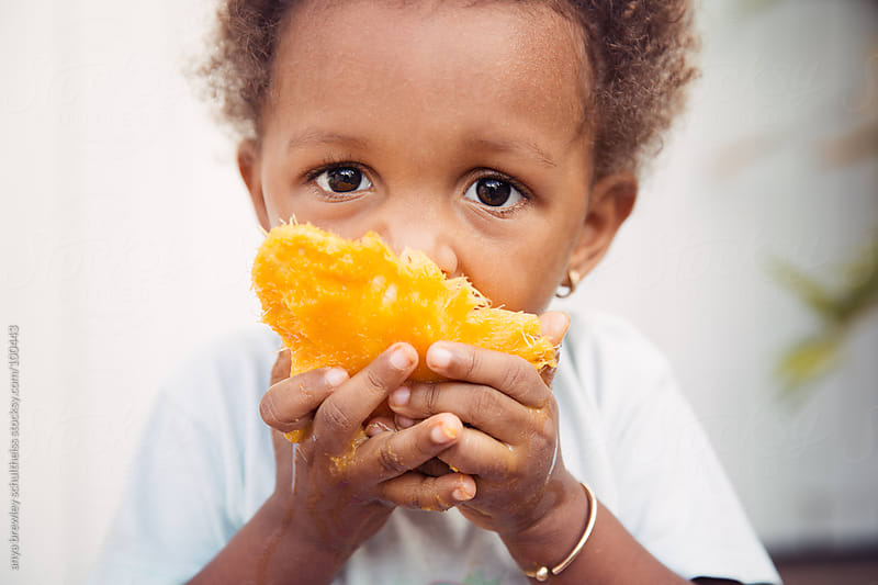 Close up of child eating a ripe mango by anya brewley schultheiss for Stocksy United