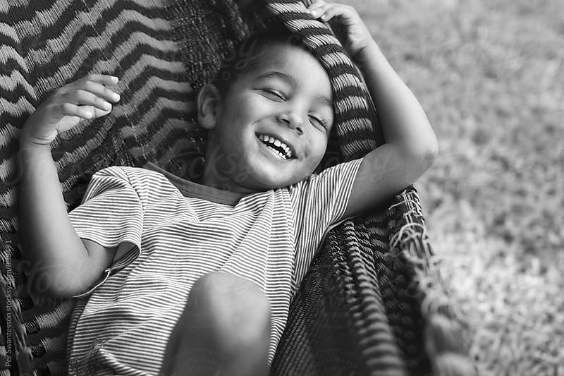 Happy boy in a hammock by Per Swantesson for Stocksy United