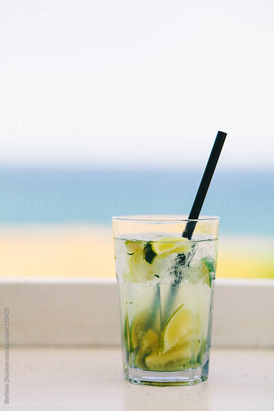 Summer cocktail - Mojito with black straw on wooden ledge by Borislav Zhuykov for Stocksy United