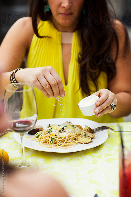 Woman Putting Cheese on Spaghetti at Dinner by Sara Remington for Stocksy United