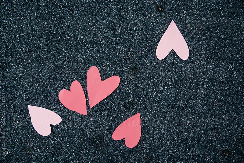 Pink paper heart shapes scattered on the ground by Gabriel (Gabi) Bucataru for Stocksy United