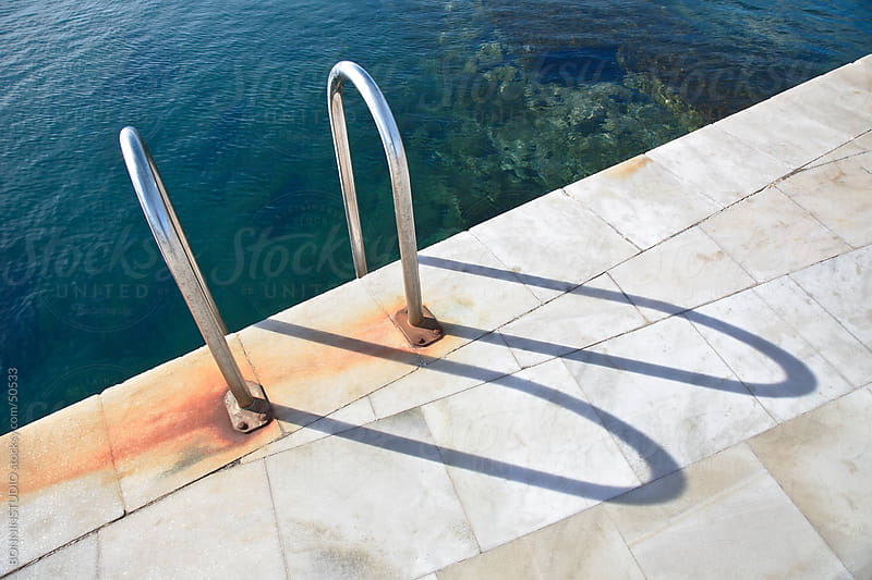 A view of a light clear blue beach water with steel ladder. by BONNINSTUDIO for Stocksy United