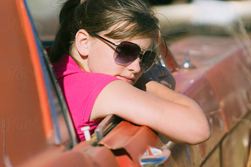 A teenager wearing sunglasses leans an arm out an old car window.  by Tana Teel for Stocksy United