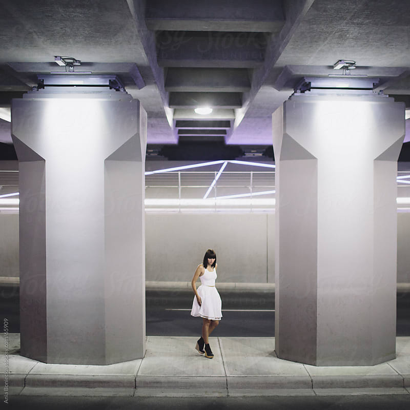 Girl in a white skirt outdoors on streets at night by Ania Boniecka for Stocksy United