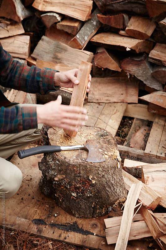 Man chopping and gathering wood for a winter fire by Trinette Reed for Stocksy United