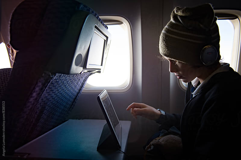 Boy in profile wearing headphones over a woollen hat while playing on a tablet screen on an airplane by Angela Lumsden for Stocksy United