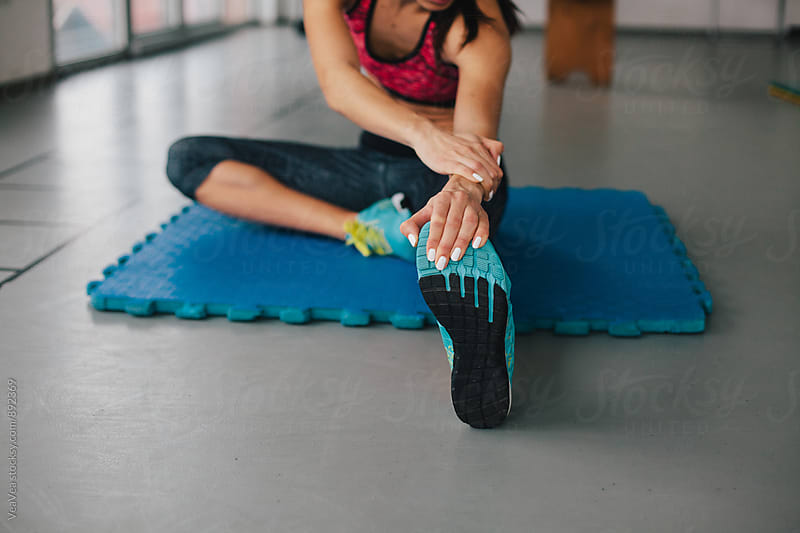Woman doing stretching exersice in the gym  by Marija Mandic for Stocksy United