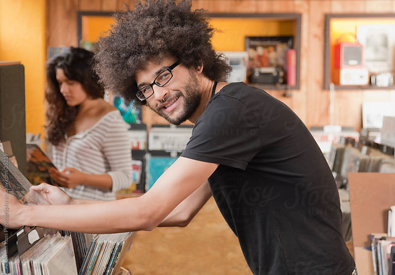 Portrait of young man browsing records at record shop by Andersen Ross Photography for Stocksy United