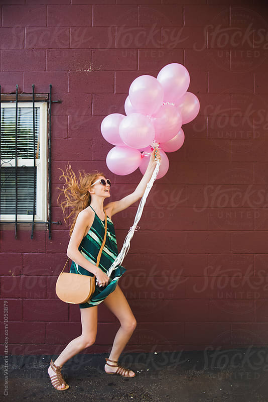 A young woman holding balloons by Chelsea Victoria for Stocksy United