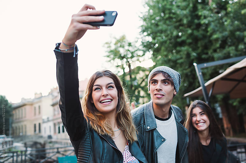 Group of friends taking a selfie together with cell by michela ravasio for Stocksy United