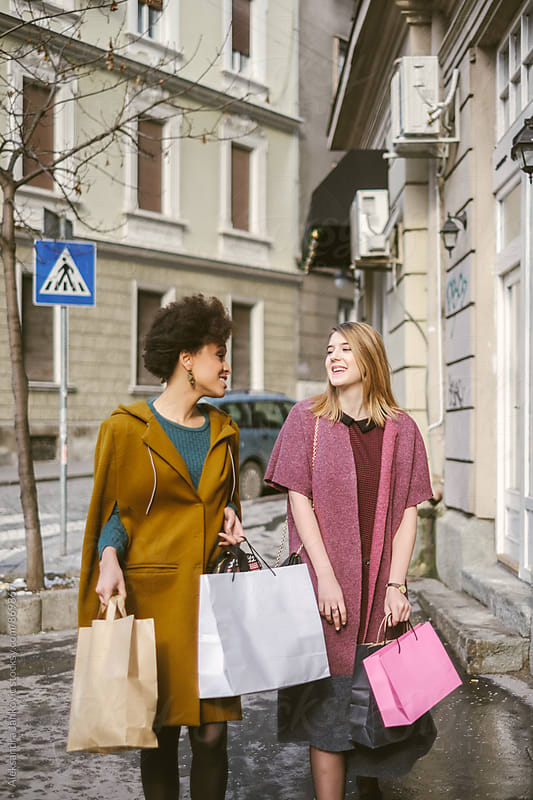 Two Women with Shopping Bags Walking Down the Street by Aleksandra Jankovic for Stocksy United