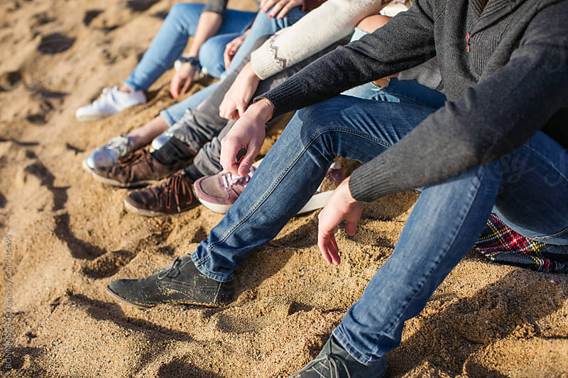 Closeup of legs of friends sitting on the beach. by BONNINSTUDIO for Stocksy United