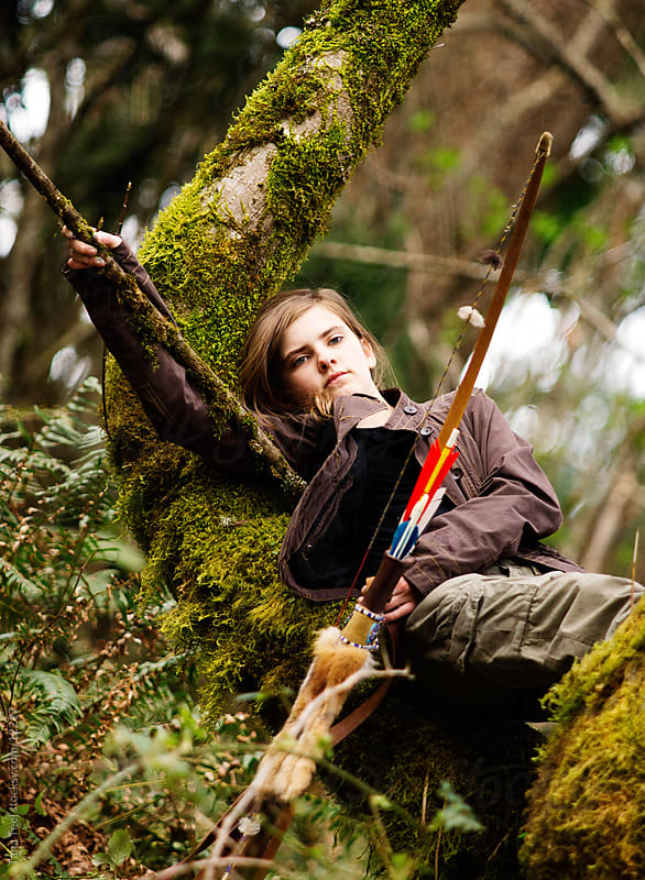 A young girl relaxing in tree holding bow and arrow.  by Tana Teel for Stocksy United