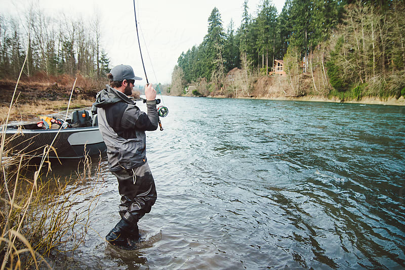 Fly fisherman standing in river fighting a large fish he is hooked up to. by Kate Daigneault for Stocksy United