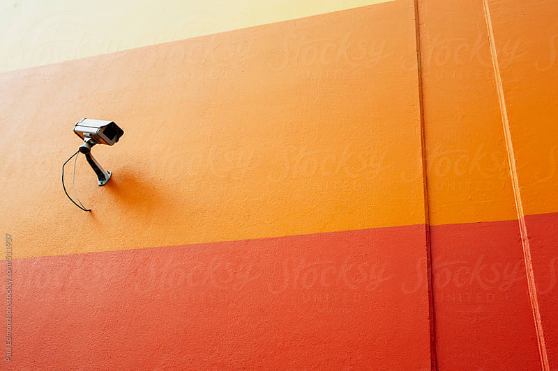 Surveillance camera on colorful building wall by Paul Edmondson for Stocksy United