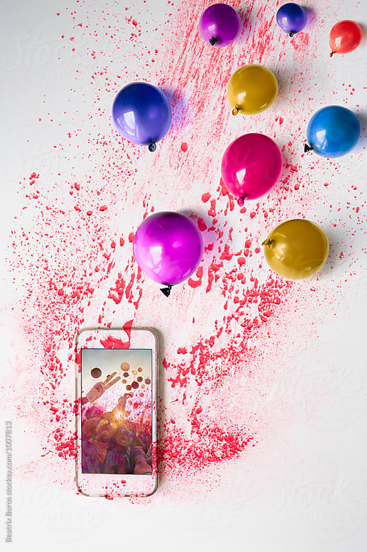 Conceptual photo of a cellphone showing a party concert imagesurrounded by colorul balloons and holi by Beatrix Boros for Stocksy United