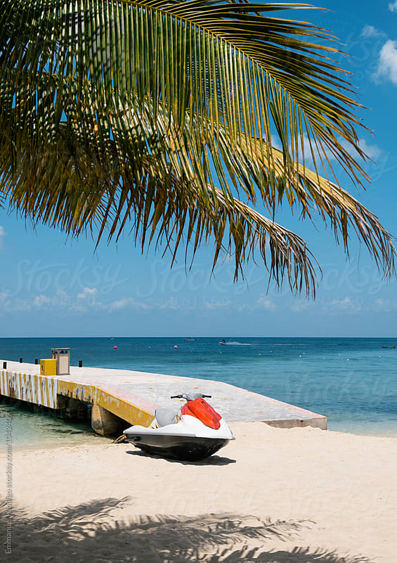 A jet ski sits along the beach at Cozumel, Mexico by Emmanuel Hidalgo for Stocksy United