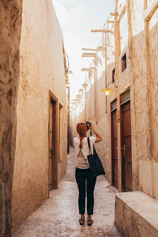 Female photographer taking photos in a small passage by Maja Topcagic for Stocksy United