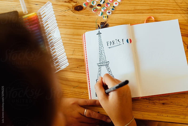 teen drawing Eiffel tower in journal by Léa Jones for Stocksy United