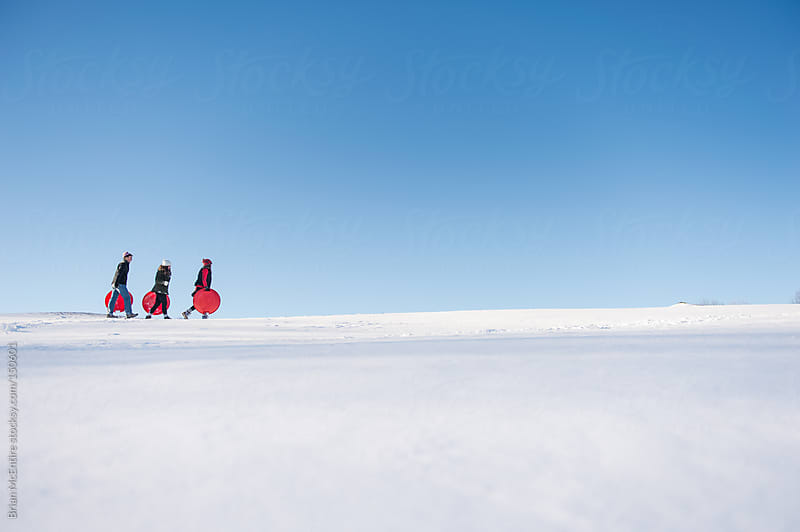 Young adults trek along a ridge line on a snow covered hill by Brian McEntire for Stocksy United