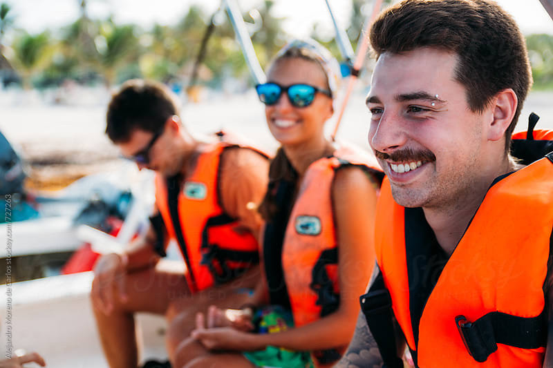 Group of happy friends with life jackets on a boat during their vacation by Alejandro Moreno de Carlos for Stocksy United