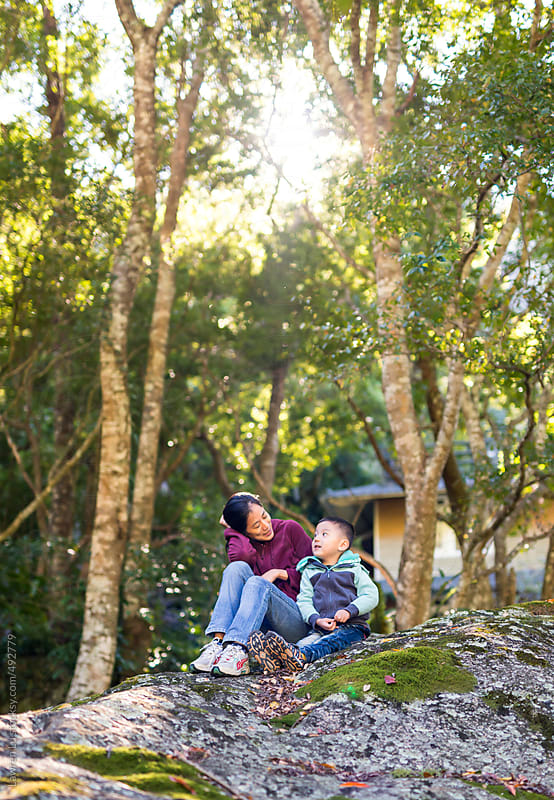 Mother and kid sitting on rock in forest by Lawren Lu for Stocksy United