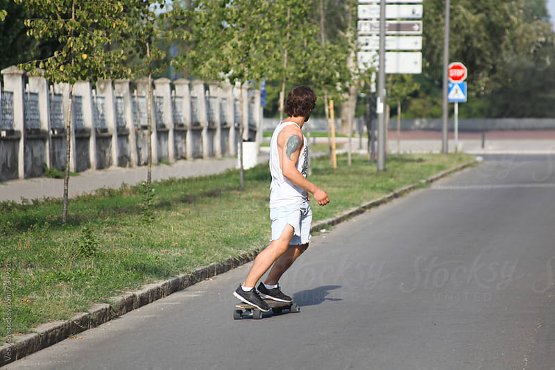 Man riding a longboard in the street by VeaVea for Stocksy United