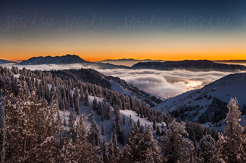 Snow Covered Rocky Mountains with Fog in Valleys at Night by Odyssey Stock for Stocksy United