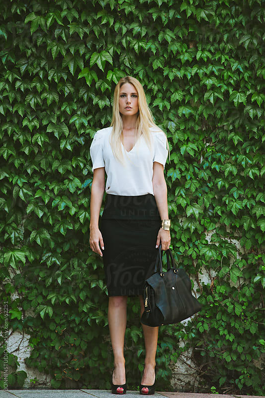 Young businesswoman with big bag on a climbing plant background. by BONNINSTUDIO for Stocksy United
