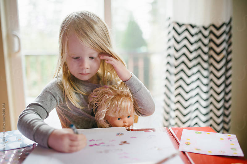 A Little Girl Drawing with her Doll by Amanda Voelker for Stocksy United