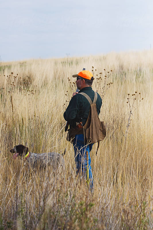 A hunter with his dog searching for fowl in a grassy field by Tana Teel for Stocksy United