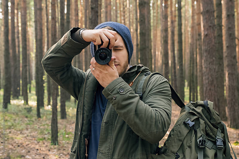 Man in blue hat photographing with camera in forest by T-REX & Flower for Stocksy United